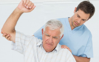 Caregiver helping male senior with stretches