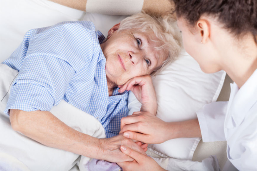Senior woman in bed receiving in home palliative care